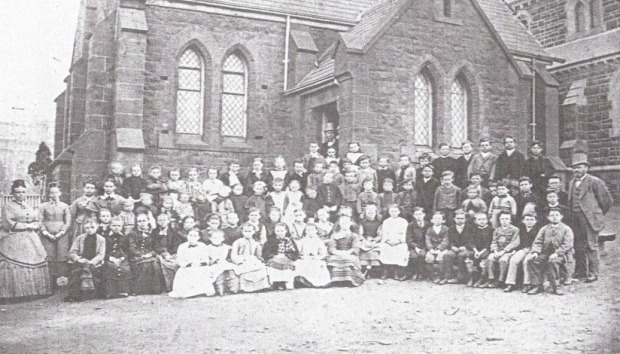Teachers and Students of the East Melbourne School in the churchyard in front of the school hall, c. 1870s.